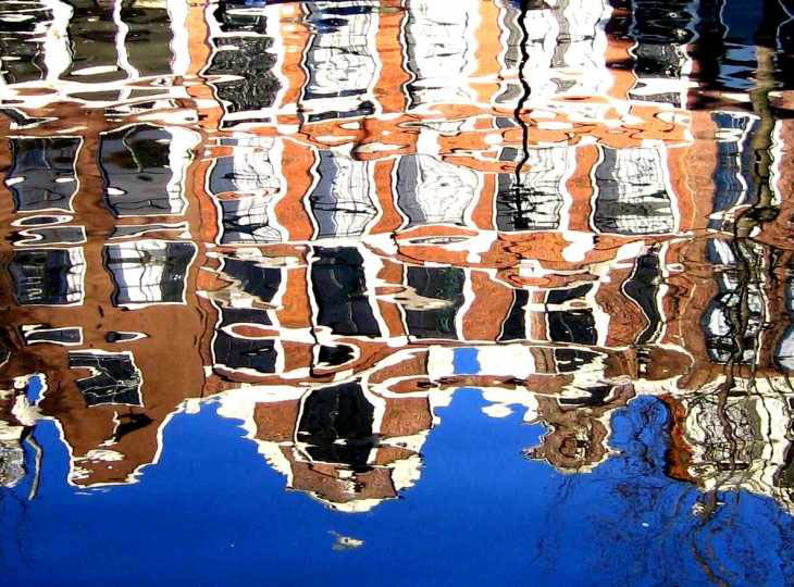 Dutch houses reflected in canal in Amsterdam