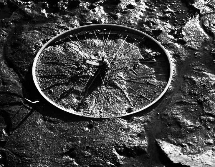 Black & white photograph. Wheel in mud