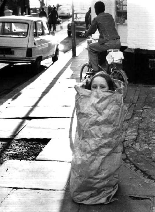Black & white photograph. Girl playing in paper bag