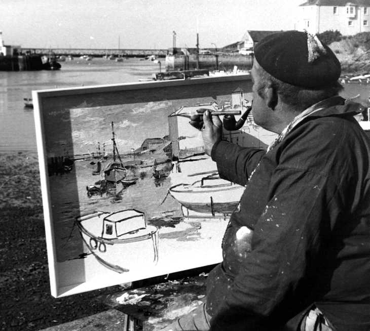 Black and white photo of painter painting on quayside