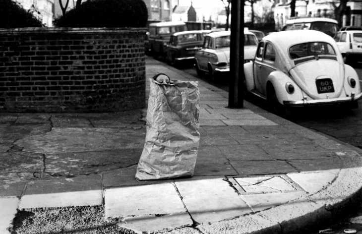 Girl playing in paper sack, West London
