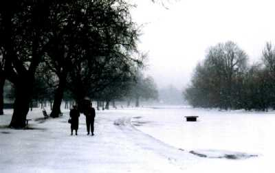 Couple by frozen lake, London, Regent's Park in snow